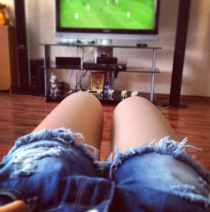 Женские ножки, смотрящие футбол